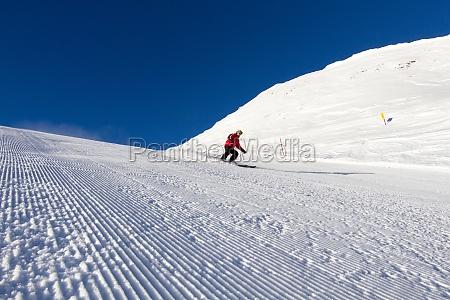 skier on groomed ski slope