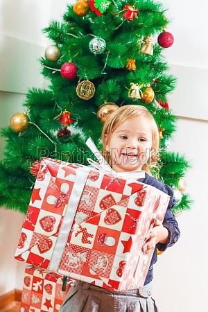 little girl holding a christmas gift