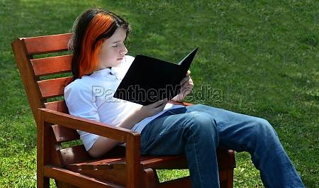 boy reading on bench in grass