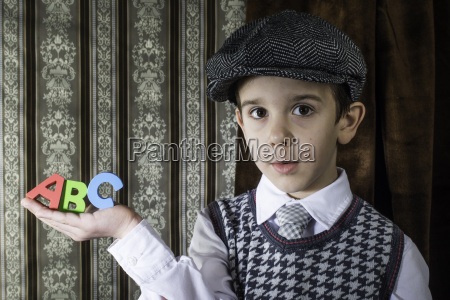 child in vintage clothes hold letters