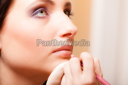 makeup artist applying with pencil cosmetic