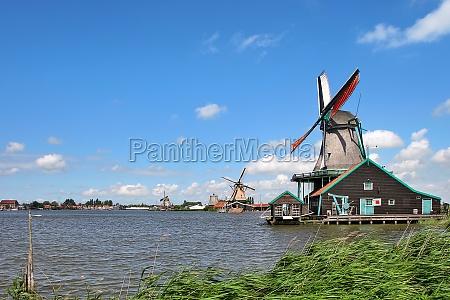 wooden windmills along river under beautiful