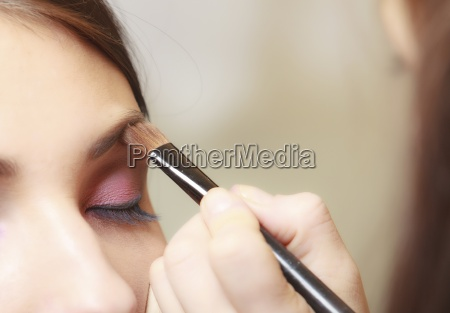 makeup artist applying cosmetic brush on