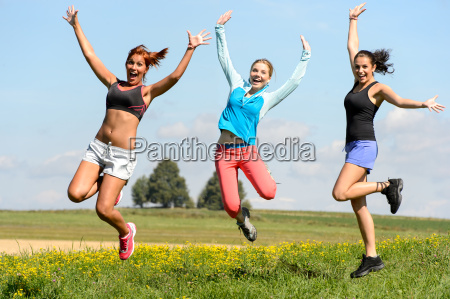 sporty friends jumping cheerful on sunny