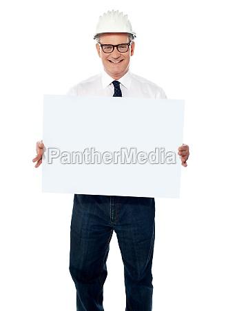 senior architect holding blank billboard