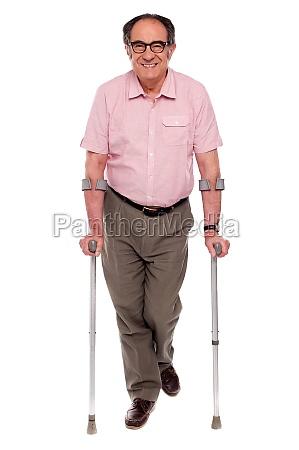 smiling senior man walking with two