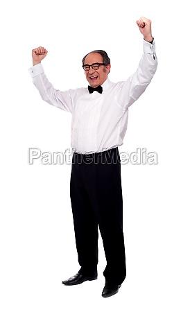 excited senior man posing with raised