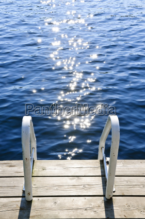 dock on summer lake with sparkling