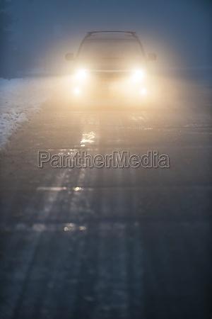 headlights of car driving in fog