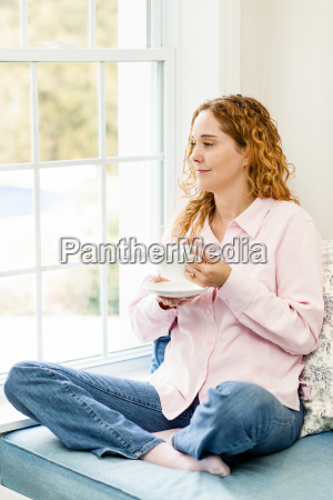woman relaxing by the window with