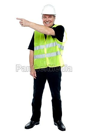 cheerful estate engineer indicating sideways