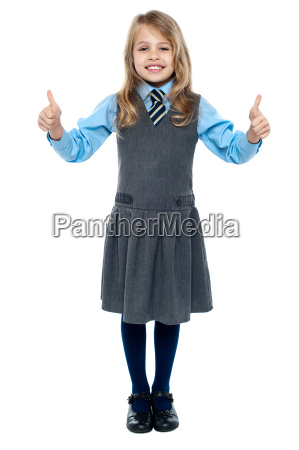 pretty school child showing thumbs up