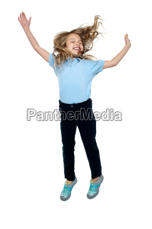 delighted young girl jumping high in