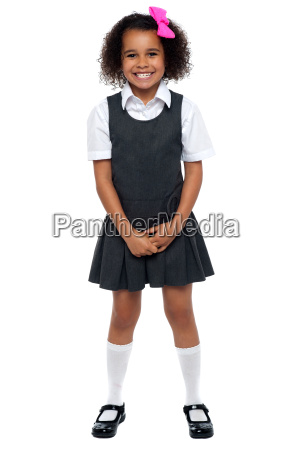 cheerful young kid in pinafore dress