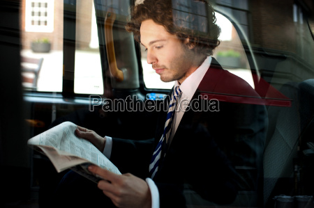 man reading newspaper inside taxi cab