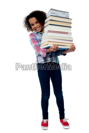 cheerful schoolgirl carrying pile of books