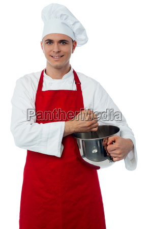 smiling confident chef holding vessel
