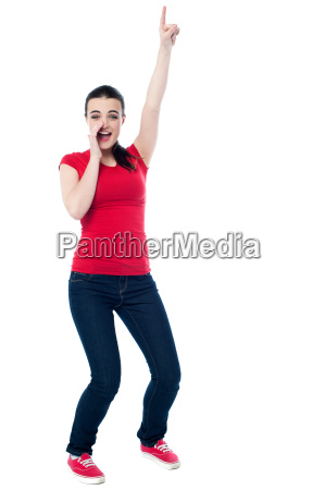excited young woman pointing upwards