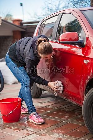 slim woman washing red car door