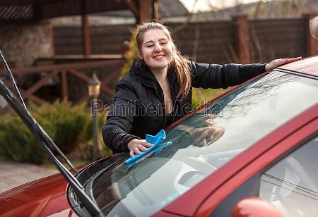 smiling woman washing car windscreen at