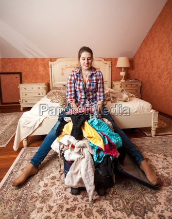 woman packing suitcase for vacation in
