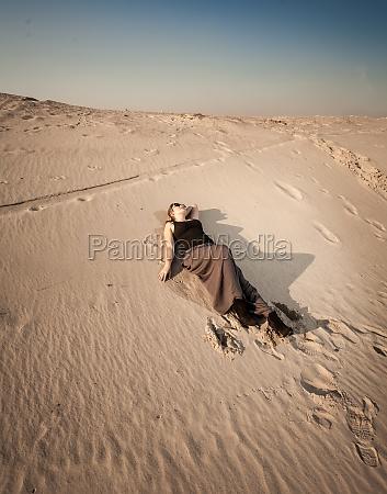 woman in dress lying on sand