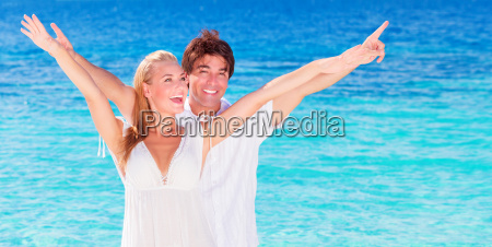 happy couple playing on the beach