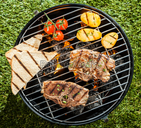 grilling lamb chops and vegetables on