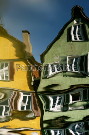 houses are reflected in the river