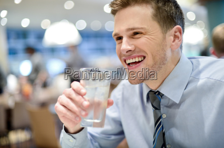 smiling young man drinking water in