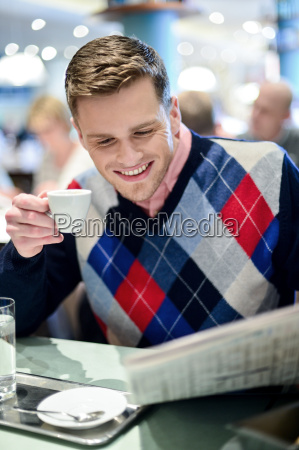 stylish man reading newspaper at outdoor