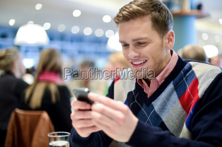 young man in cafe and using