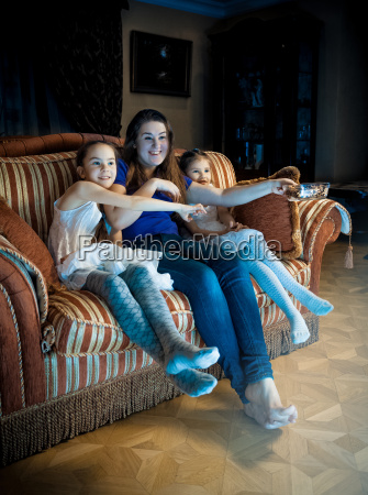 family with kids watching tv at