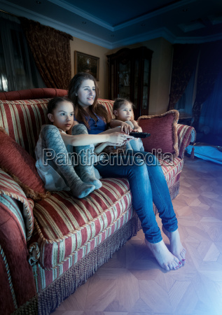 mother with two daughters watching horror
