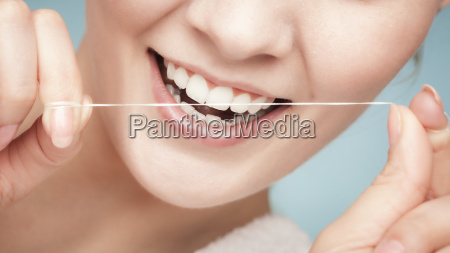 girl cleaning teeth with dental floss