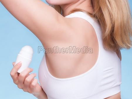 girl applying deodorant stick in the
