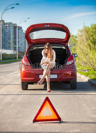 depressed woman sitting on trunk of
