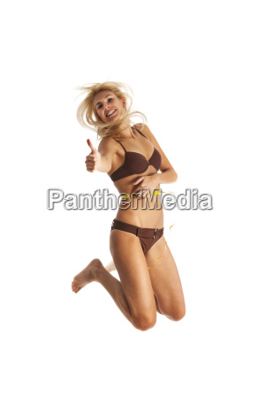 woman jumps with measuring tape