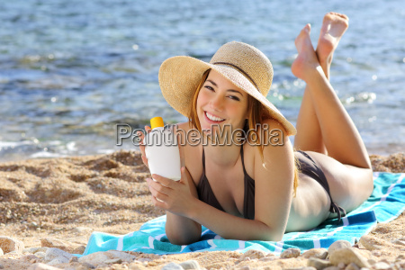 happy woman holding a sunscreen bottle