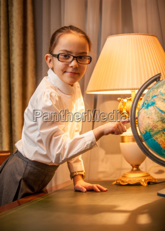girl in eyeglasses pointing at globe