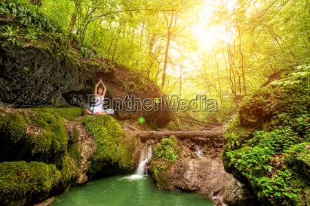 woman practices yoga at the waterfall