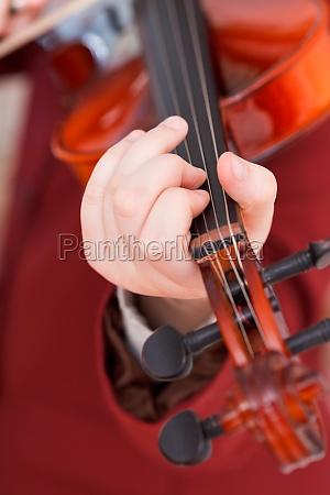 girl playing violin chord on