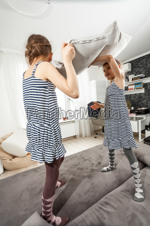 little girl fighting with pillows on