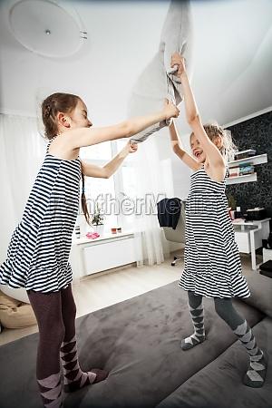 little girls pillow fighting in bedroom