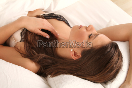 woman in bra at the bed