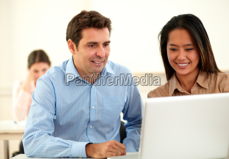 adult professional couple looking at laptop