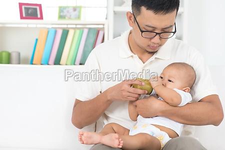 father bottle feeding baby