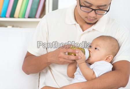 father bottle feeding baby at home