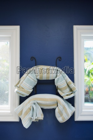 striped towels on rack on blue