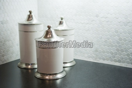 cannisters on countertop infront of tile